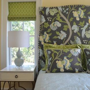 ブリッジポートの広いトランジショナルスタイルのおしゃれな主寝室 (黄色い壁、無垢フローリング、暖炉なし、茶色い床) のインテリア