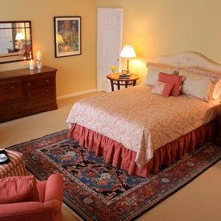 Ejemplo de dormitorio tradicional, sin chimenea, con moqueta y paredes amarillas