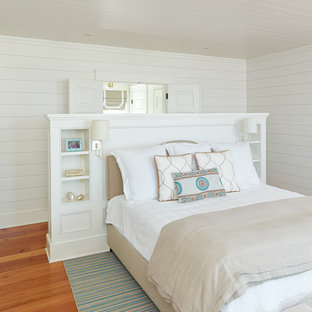 Tropical guest bedroom in Charleston with white walls, medium hardwood floors and no fireplace.