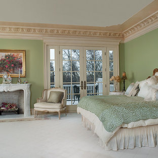 Photo of an expansive traditional master bedroom in Grand Rapids with green walls, marble floors, a standard fireplace and a stone fireplace surround.