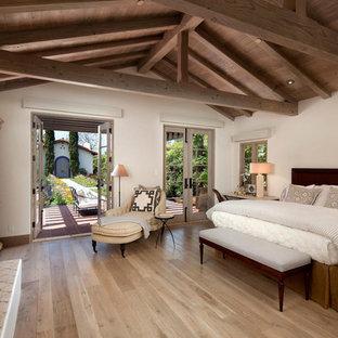 Immagine di una camera da letto mediterranea con pareti beige, parquet chiaro e camino classico