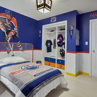 Imagen de habitación de invitados moderna, de tamaño medio, sin chimenea, con paredes azules y suelo laminado