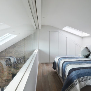 Photo of a small contemporary mezzanine bedroom in London with white walls, light hardwood flooring and no fireplace.