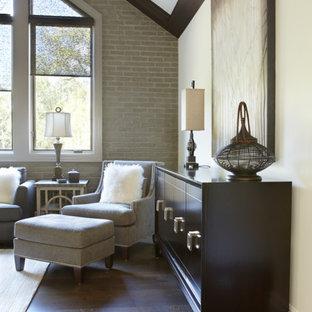 Diseño de dormitorio tipo loft, clásico renovado, grande, con paredes grises, suelo de madera oscura, chimenea tradicional y marco de chimenea de piedra