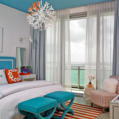 Mid-sized beach style master light wood floor and gray floor bedroom photo in Miami with white walls and no fireplace
