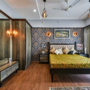 Immagine di una grande camera da letto moderna con pareti grigie, pavimento in legno massello medio e pavimento marrone