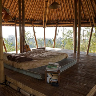 Diseño de dormitorio exótico, sin chimenea, con suelo de bambú
