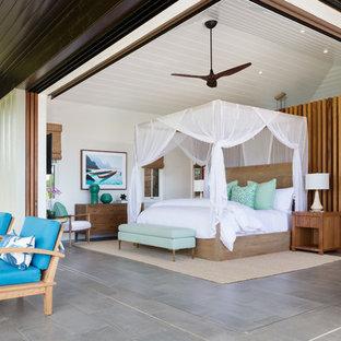 Ispirazione per una camera matrimoniale tropicale di medie dimensioni con pareti bianche, pavimento grigio, pavimento con piastrelle in ceramica e nessun camino