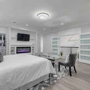 バンクーバーの広いコンテンポラリースタイルのおしゃれな主寝室 (グレーの壁、淡色無垢フローリング、横長型暖炉、木材の暖炉まわり、茶色い床) のインテリア