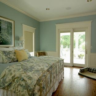 Immagine di una grande camera matrimoniale country con pareti blu e pavimento in legno massello medio