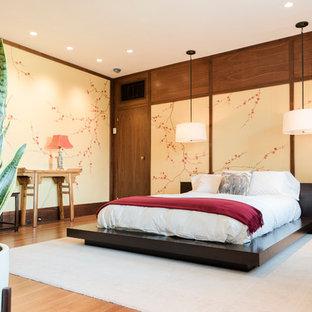 Example of a zen medium tone wood floor and brown floor bedroom design in New York with beige walls
