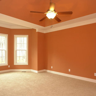 Large transitional master carpeted bedroom photo in Raleigh with orange walls