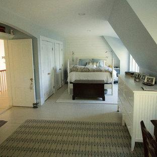 Modelo de dormitorio tradicional, de tamaño medio, con chimenea tradicional, marco de chimenea de ladrillo, paredes blancas y suelo de madera clara