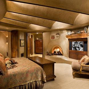 Diseño de dormitorio principal, de estilo americano, con paredes beige, moqueta, chimenea tradicional, marco de chimenea de yeso y suelo beige