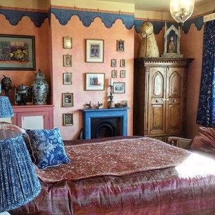Ispirazione per una grande camera degli ospiti etnica con pareti arancioni, moquette, camino classico, cornice del camino in legno e pavimento beige