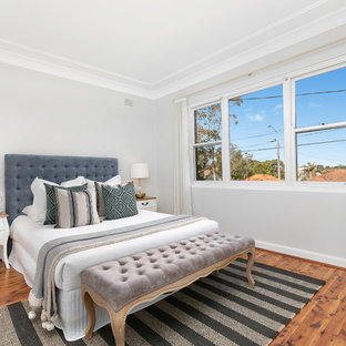 Inspiration for a small transitional master bedroom in Sydney with grey walls, medium hardwood floors and brown floor.