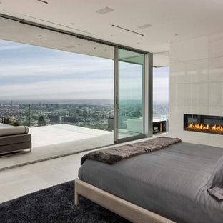 На фото: спальня в современном стиле с горизонтальным камином и фасадом камина из плитки