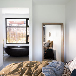 This is an example of an industrial bedroom in Melbourne with white walls, concrete floors and grey floor.