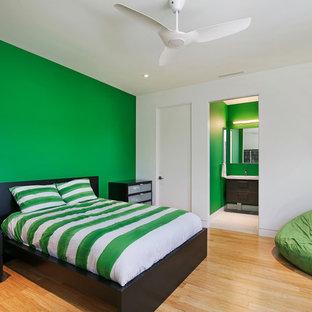 Imagen de habitación de invitados moderna, de tamaño medio, sin chimenea, con paredes verdes, suelo de bambú y suelo multicolor