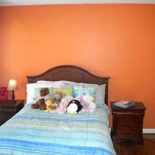 Ejemplo de habitación de invitados clásica, pequeña, sin chimenea, con parades naranjas y suelo de madera oscura