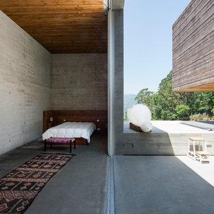 他の地域のコンテンポラリースタイルのおしゃれな寝室 (グレーの壁、コンクリートの床、グレーの床)