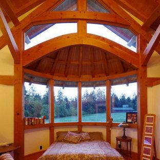Modelo de dormitorio principal, grande, con paredes blancas, suelo de madera en tonos medios, chimenea de esquina y marco de chimenea de madera