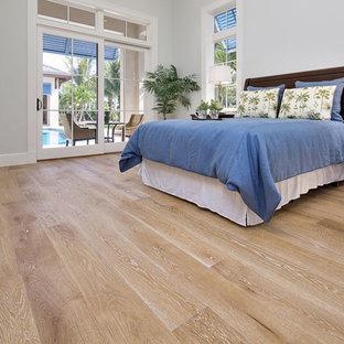 Modelo de dormitorio principal, tropical, grande, con paredes grises y suelo de madera clara