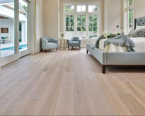 Example Of A Large Cottage Chic Master Light Wood Floor Bedroom Design In New York With