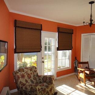 Modelo de dormitorio principal, de tamaño medio, con parades naranjas y suelo de baldosas de cerámica