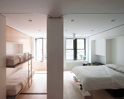 Example of a small minimalist bedroom design in New York with white walls