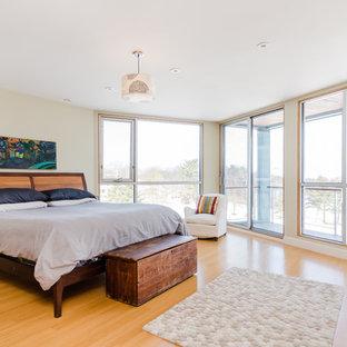 Example Of A Large Danish Master Light Wood Floor And Beige Bedroom Design In Boston