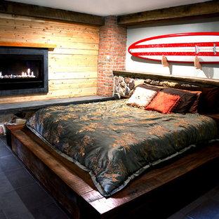 フィラデルフィアの中サイズのコンテンポラリースタイルのおしゃれな主寝室 (グレーの壁、スレートの床、標準型暖炉、木材の暖炉まわり) のインテリア