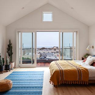 Imagen de dormitorio principal, moderno, con paredes blancas, suelo de madera clara, estufa de leña y marco de chimenea de metal