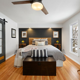 Example of a small transitional master medium tone wood floor and brown floor bedroom design in Kansas City with white walls