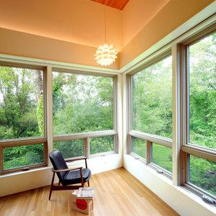 Immagine di una camera da letto design con pareti arancioni e parquet chiaro