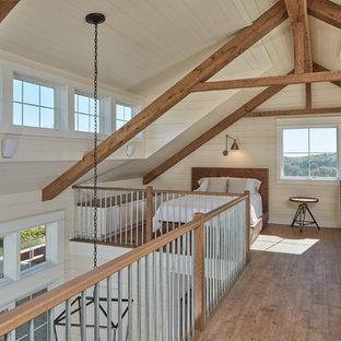 Imagen de dormitorio tipo loft, de estilo de casa de campo, con suelo de madera en tonos medios, suelo marrón y paredes beige