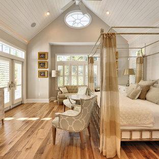 Diseño de dormitorio costero con paredes beige y suelo de madera en tonos medios