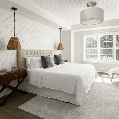 Large farmhouse master brown floor and dark wood floor bedroom photo in Charlotte with gray walls