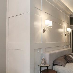 Diseño de dormitorio principal, urbano, grande, con paredes beige, suelo de baldosas de cerámica, chimenea tradicional, marco de chimenea de piedra y suelo beige