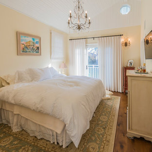 This is an example of a mid-sized beach style guest bedroom in Los Angeles with yellow walls, medium hardwood floors, no fireplace and brown floor.