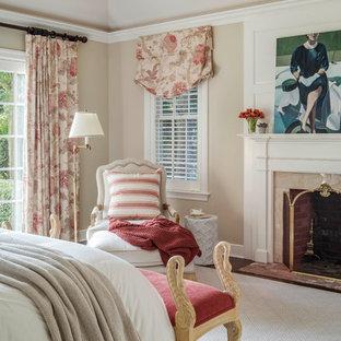 Modelo de dormitorio principal, clásico renovado, de tamaño medio, con paredes beige, moqueta, chimenea tradicional y marco de chimenea de hormigón