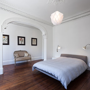 Large Eclectic Bedroom In London With White Walls And Dark Hardwood  Flooring.