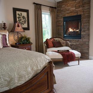 Idee per un'ampia camera matrimoniale stile americano con pareti beige, moquette, camino bifacciale, cornice del camino in pietra e pavimento beige