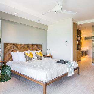 Diseño de dormitorio principal, exótico, grande, sin chimenea, con paredes blancas, suelo de madera clara y suelo beige