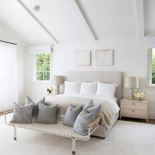Modelo de habitación de invitados clásica renovada, grande, con paredes beige, suelo de madera en tonos medios y suelo marrón