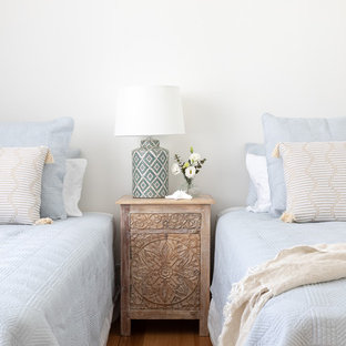 This is an example of a beach style bedroom in Other with white walls, medium hardwood floors and brown floor.