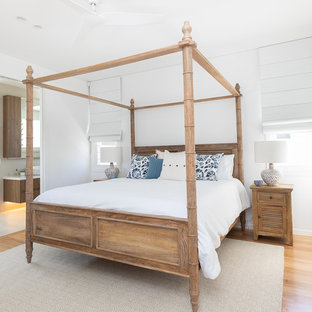 Design ideas for a beach style bedroom in Other with white walls, medium hardwood floors and brown floor.