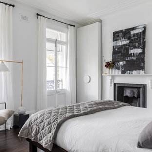 Photo of a contemporary master bedroom in Sydney with white walls, dark hardwood floors, a standard fireplace and brown floor.
