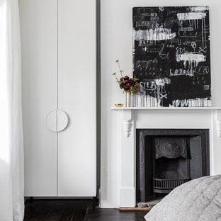 Idéer för ett mellanstort modernt gästrum, med vita väggar, mörkt trägolv, en standard öppen spis och en spiselkrans i metall