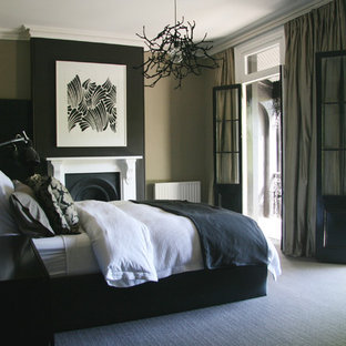 Contemporary bedroom in Sydney with black walls, carpet, a standard fireplace and grey floors.